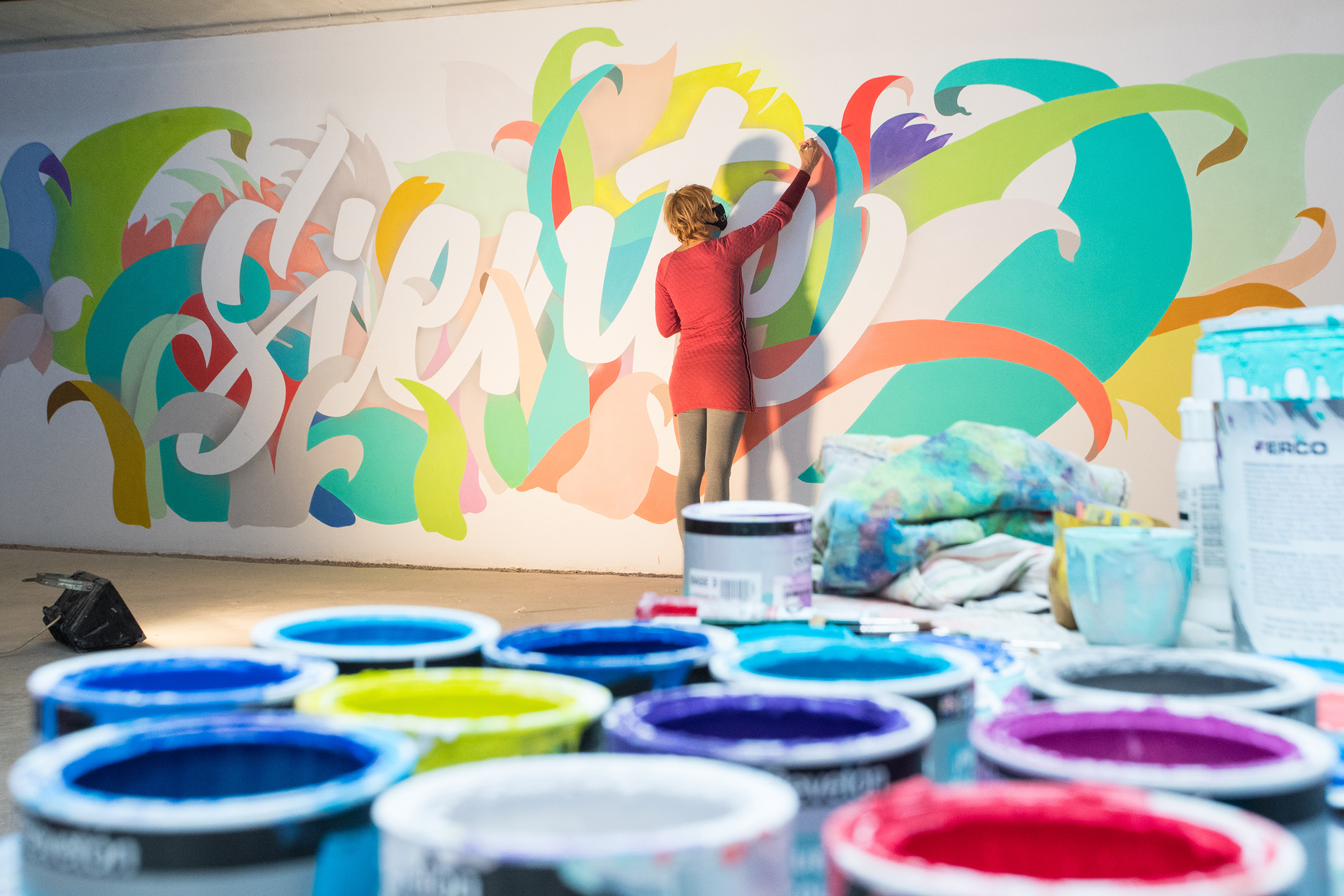 Noe pintando el mural Siente en Residencial Novelty Plaza, de Aransa